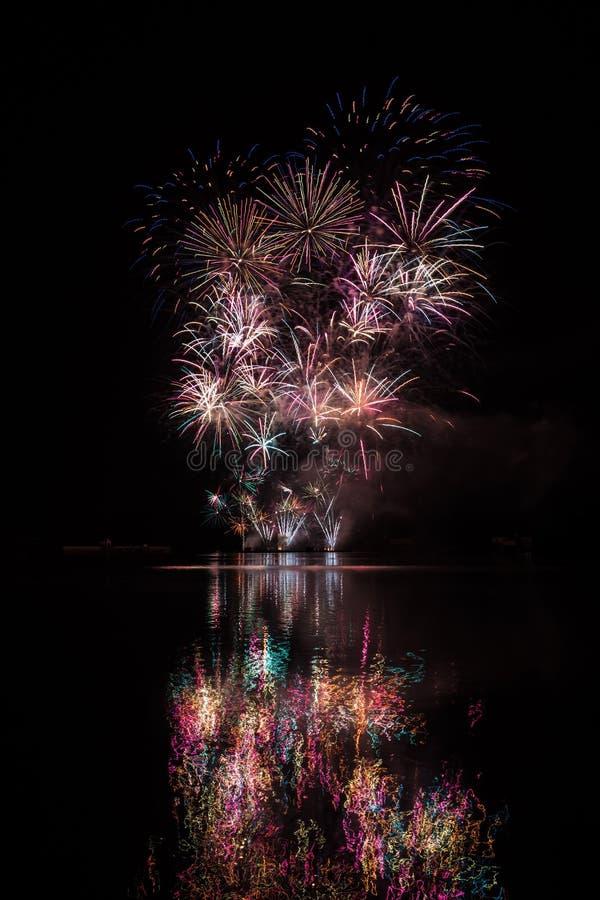 Duży skwarkowy wybuch w bogatych fajerwerkach nad Brno tamą z jeziornym odbiciem zdjęcie stock