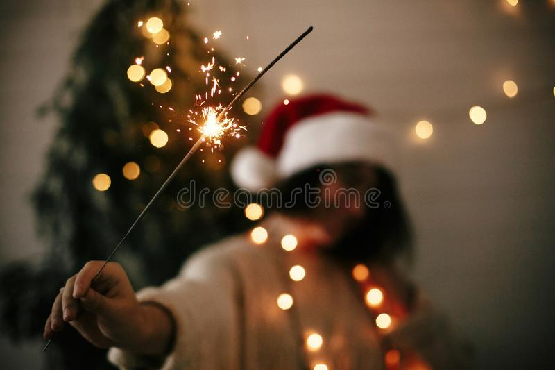 Duży sparkler palenie w ręce elegancka dziewczyna w Santa kapeluszu na tle nowożytny choinki światło w ciemnym pokoju Kobieta z obrazy stock