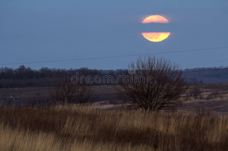 Duży srebny rozjarzony księżyc zakończenie na zmroku - niebieskie niebo z rozrzuconymi chmurami fotografia stock