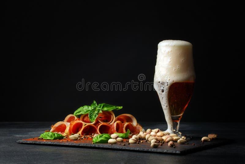 Duży szklany pełny lekki piwo z pianą, wyśmienicie prosciutto i szpinakiem na czarnym tle, Pistacje blisko obrazy royalty free