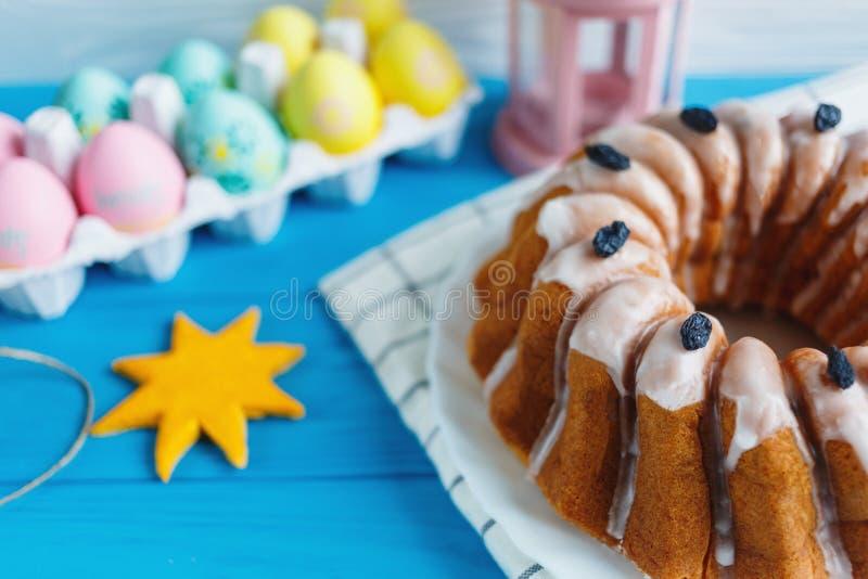 Duży talerz z tortem i ręką malował kolorowych jajka na ręczniku na błękitnym tle, z bliska Wielkanoc dekoracji obraz stock