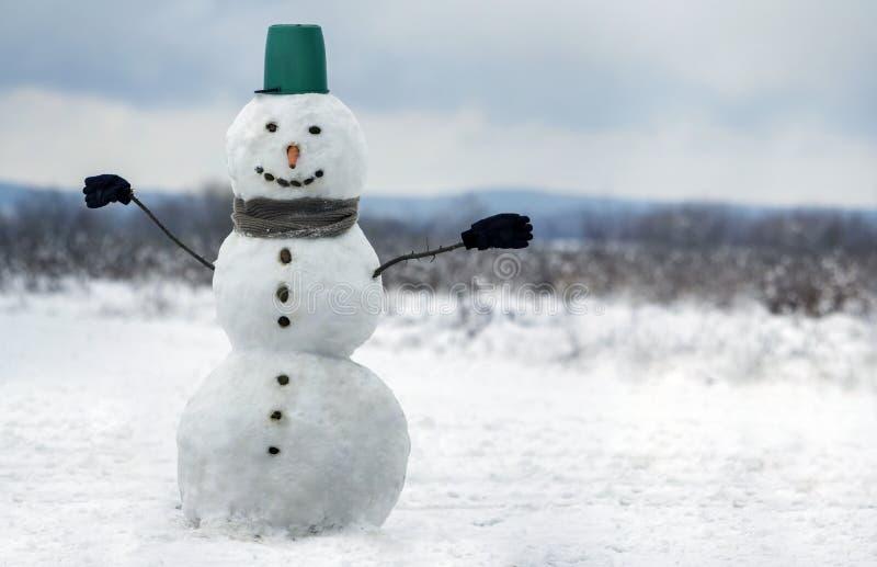 Duży uśmiechnięty bałwan z wiadro kapeluszem, szalik, rękawiczki na białym śnieżnym śródpolnym zima krajobrazie, zamazani czarni  fotografia royalty free