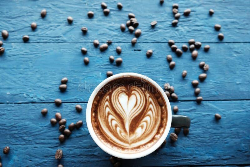 Du café de Latte est placé sur un plancher en bois bleu Il y a des grains de café autour photos libres de droits