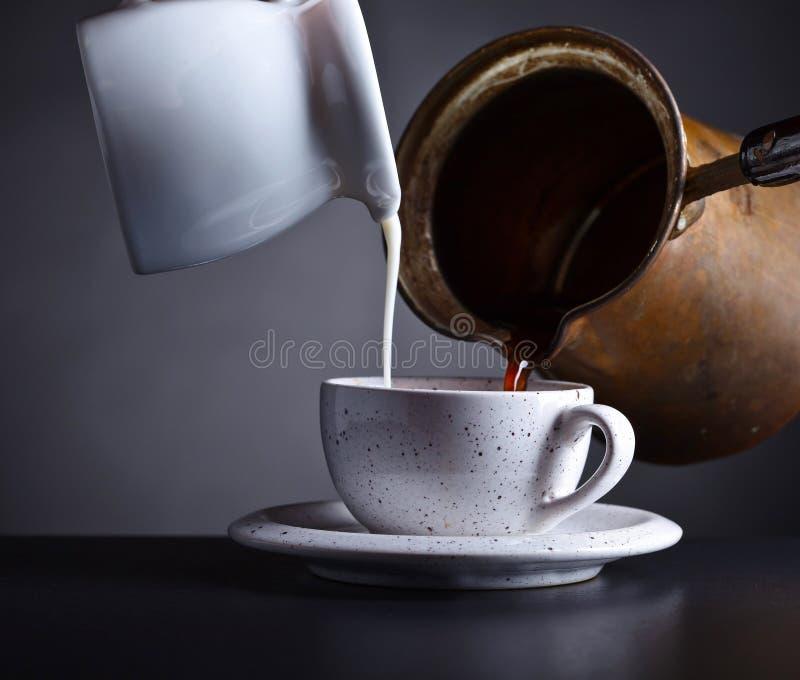 Du café et du lait chauds frais est versé dans la tasse photographie stock libre de droits