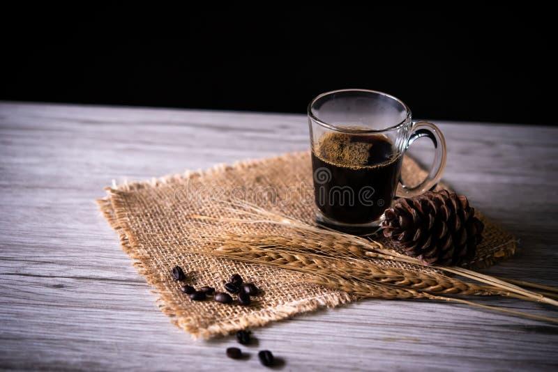 Du café noir en verre est encore placé sur le plancher en bois - concept image libre de droits