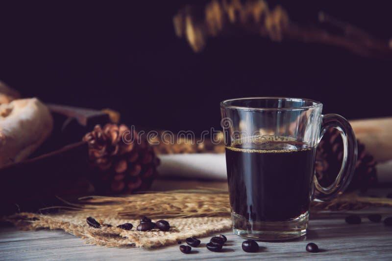 Du café noir en verre est encore placé sur le plancher en bois - concept photos stock