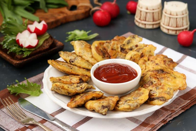 Du foie de poulet dans la pâte lisse est placé sur un plat avec la sauce tomate photos stock