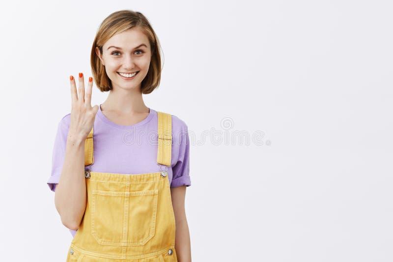 Du har tre val Lycklig glad och vänskapsmatch-seende blond kvinnlig med kort frisyr som visar få fingrar och royaltyfri foto