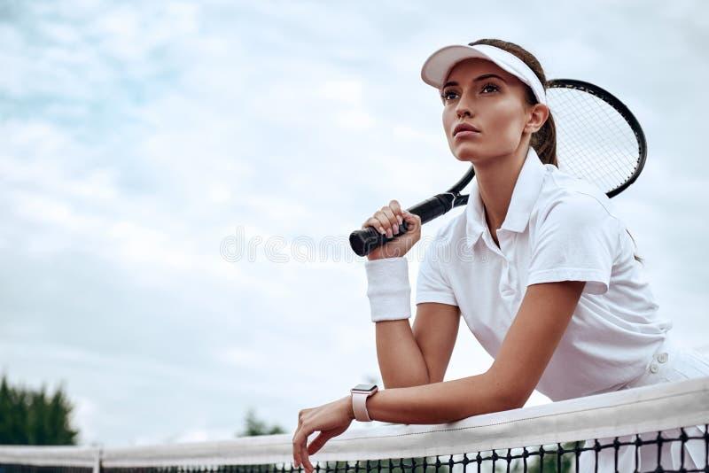 Du kan inte segra, om inte du lär hur man förlorar Stående av den unga härliga tennisspelaren med en racket på en domstol som ser royaltyfri foto