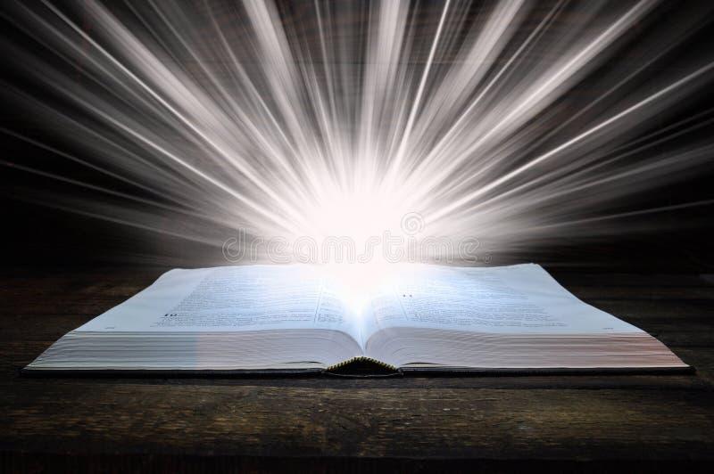 Du?a ksi??ka biblia k?ama na drewnianym stole W zmroku ?wiat?o b?yszczy na ksi??ce z g?ry ?wiat?o wynika ksi??k? fotografia stock