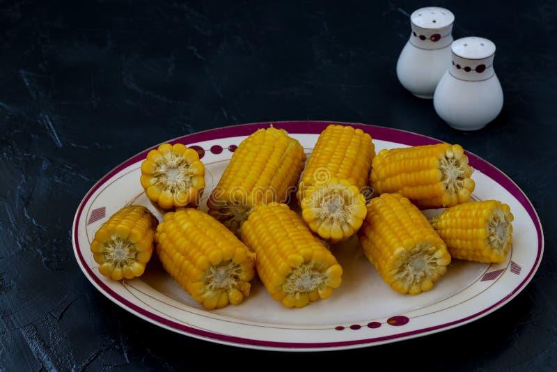Du maïs bouilli est situé sur un plat sur un fond foncé image libre de droits