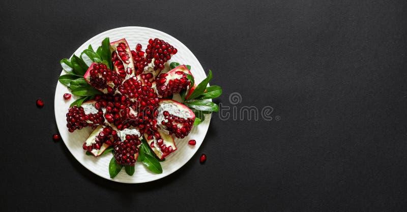 Du plat blanc un fruit cassé mûr de grenade d'isolement sur un fond noir, copient l'espace image stock