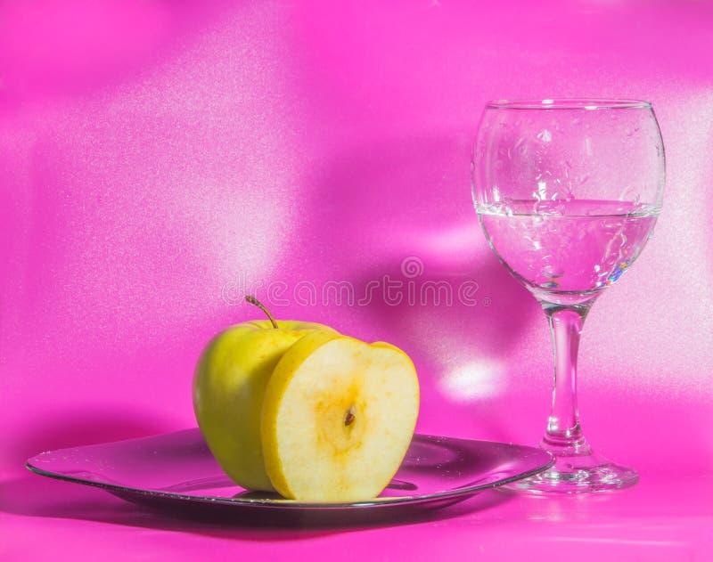 Du plat est Apple jaune avec un verre de l'eau sur un CCB rose photos libres de droits