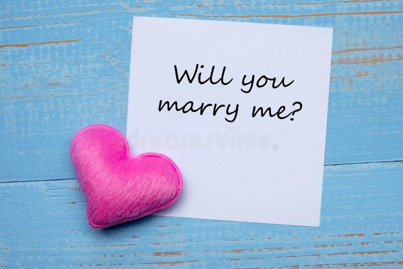 DU SKA ATT GIFTA SIG MIG? ord på pappers- anmärkning med rosa hjärtaformgarnering på blå trätabellbakgrund Förälskelse bröllop, r royaltyfri foto