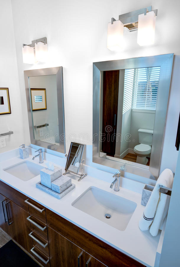 Dual Bathroom Vanity and Mirrors. Bathroom sinks and mirrors for two individuals with stained wood cabinetry stock photos