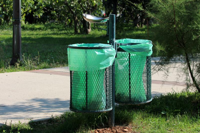 Dual outdoor metal public trash can with fresh new nylon bags inserted and ashtray on top next to concrete sidewalk in local park. Surrounded with grass and stock photo