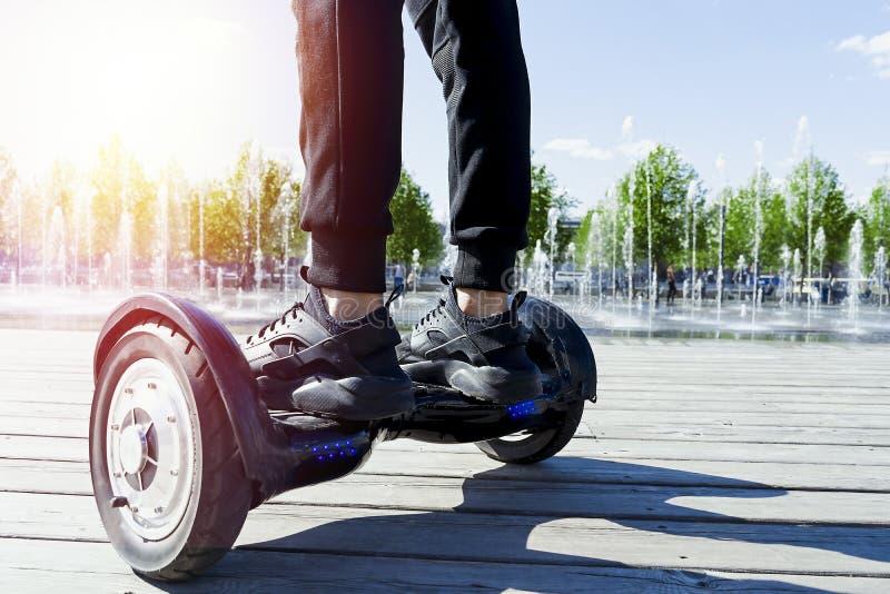 Dual Wheel Self Balancing Electric Skateboard. electrical scooter outdoors. Man riding hoverboard in the park. Close Up of Dual Wheel Self Balancing Electric stock photos