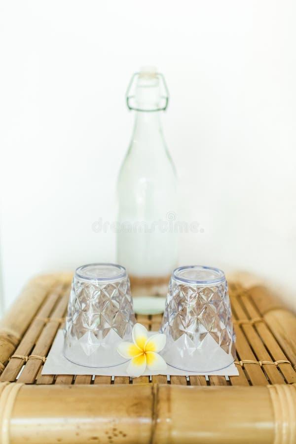 Duas águas do vidro e a de vidro de garrafa na tabela de bambu imagem de stock