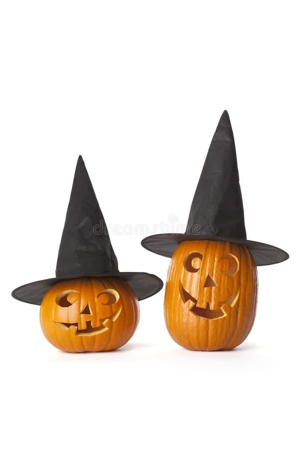 Duas abóboras de Halloween com o chapéu negro nos vagabundos brancos fotos de stock