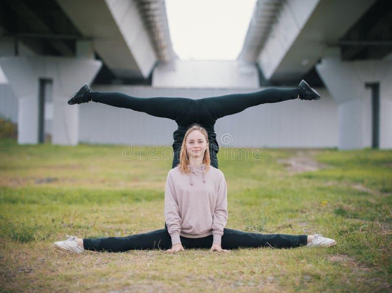 Duas acrobatas das meninas executam o suporte nas separações na grama na perspectiva da ponte fotos de stock