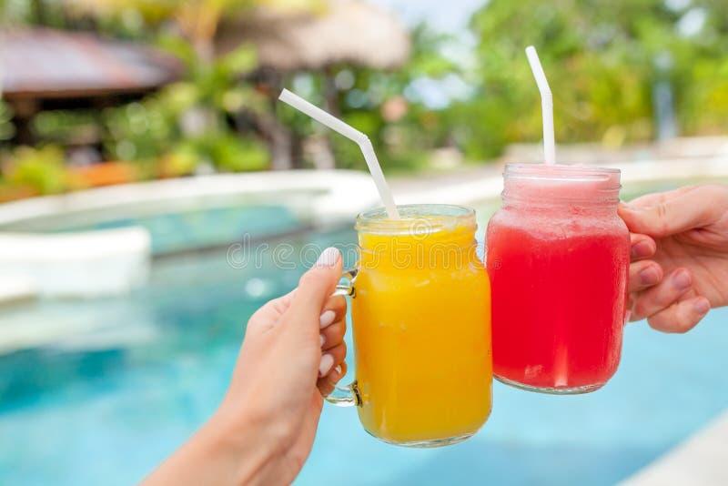 Duas agitações de fruto coloridas nas mãos verão e humor tropical Batido de fruta misturado frio das bebidas, da manga e da melan fotos de stock royalty free