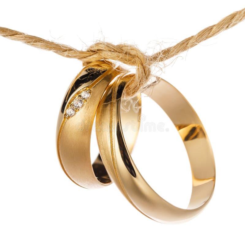 Duas alianças de casamento amarradas com uma corda como um símbolo da união de uma família nova, isolada imagens de stock royalty free