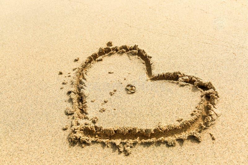 Duas alianças de casamento colocadas em um coração tirado na areia imagens de stock