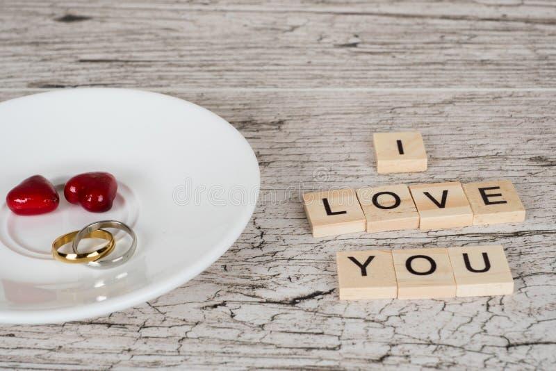 Duas alianças de casamento com corações vermelhos na placa branca fotos de stock royalty free