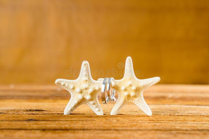 Duas alianças de casamento com a estrela do mar dois na tabela de madeira fotos de stock