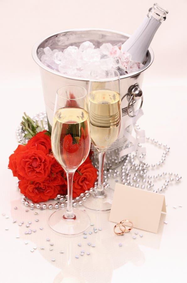 Duas alianças de casamento douradas, cartão, vidros do champanhe imagem de stock