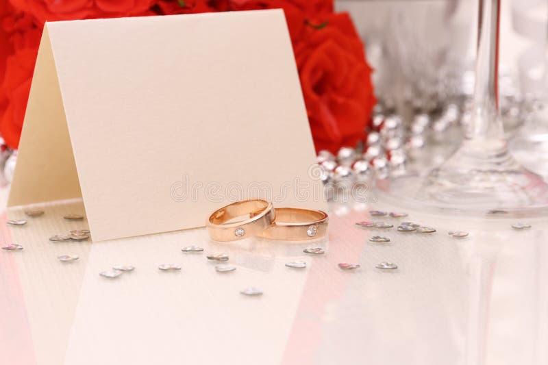 Duas alianças de casamento douradas com cartão, rosas vermelhas foto de stock royalty free