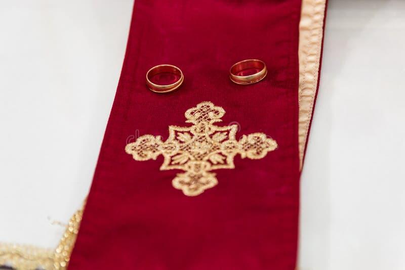 Duas alianças de casamento douradas isoladas no branco imagem de stock