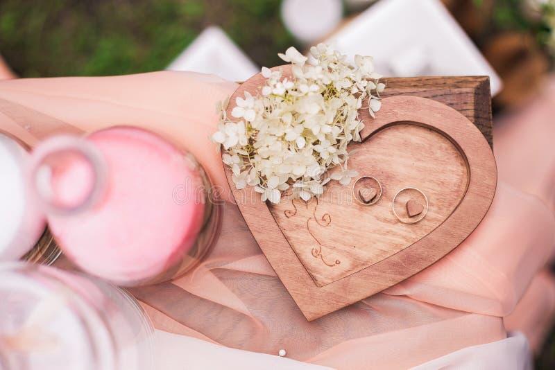 Duas alianças de casamento douradas no fundo de madeira do coração fotografia de stock royalty free