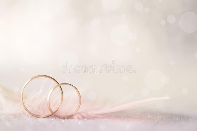 Duas alianças de casamento e penas douradas - fundo macio claro imagens de stock