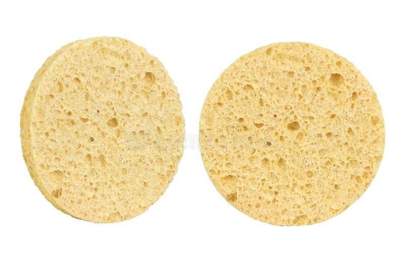 Duas almofadas cosméticas da esponja do círculo bege para a limpeza da composição da cara, uma vista frontal e uma lateral, isola imagem de stock royalty free