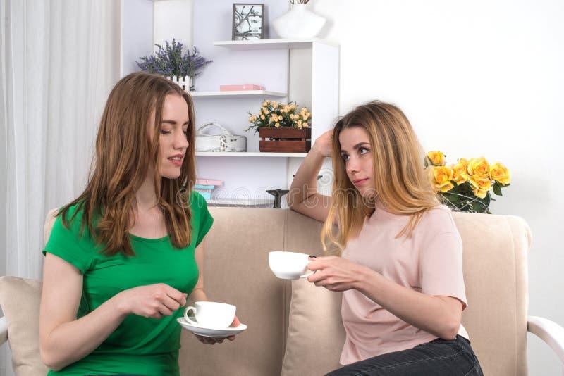 Duas amigas atrativas novas sentam-se em um sofá com o tampão do chá fotografia de stock