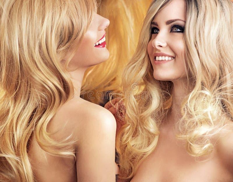 Duas amigas atrativas que tomam de seu cabelo foto de stock