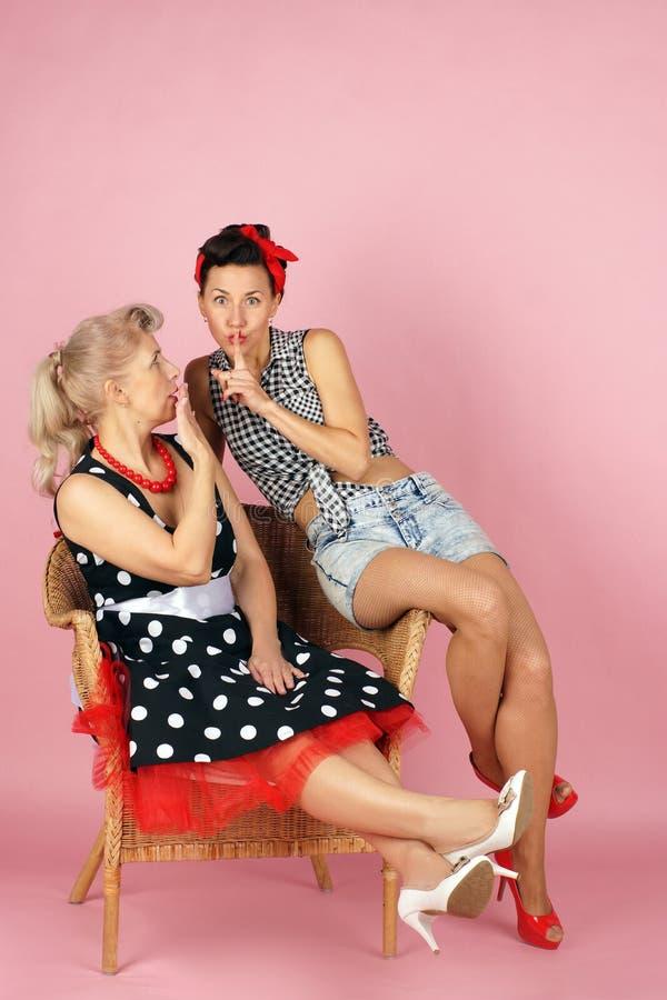 Duas amigas bonitas ao estilo da vibração do pinup e para fazer um com o otro secreto em um fundo cor-de-rosa imagens de stock