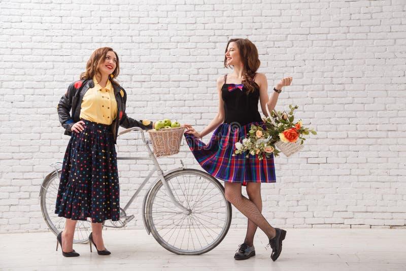 Duas amigas bonitas brilhantes novas com uma bicicleta e uma cesta das flores encontradas e da bisbolhetice foto de stock