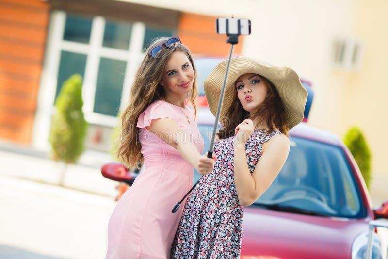 Duas amigas bonitos que tomam selfies perto do carro fotos de stock royalty free