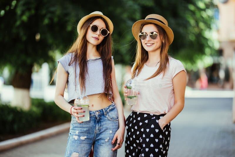 Duas amigas das meninas bebem bebidas frias do verão na rua Adultos novos foto de stock