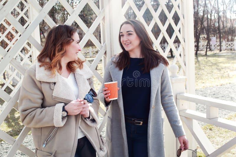 Duas amigas das mulheres bebem o café no parque fotografia de stock