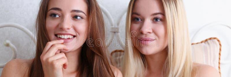 Duas amigas de sorriso felizes comem a pipoca na cama fotos de stock royalty free