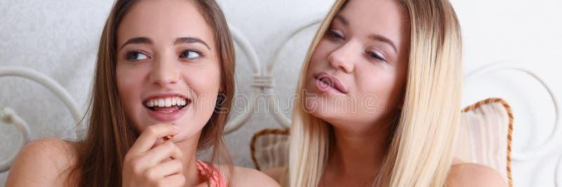 Duas amigas de sorriso felizes comem a pipoca na cama imagem de stock royalty free