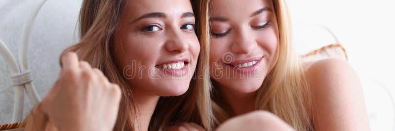 Duas amigas de sorriso felizes comem a pipoca na cama foto de stock