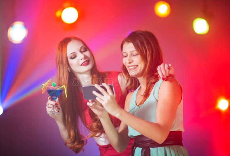 Duas amigas em um clube noturno sob o projetor imagem de stock royalty free