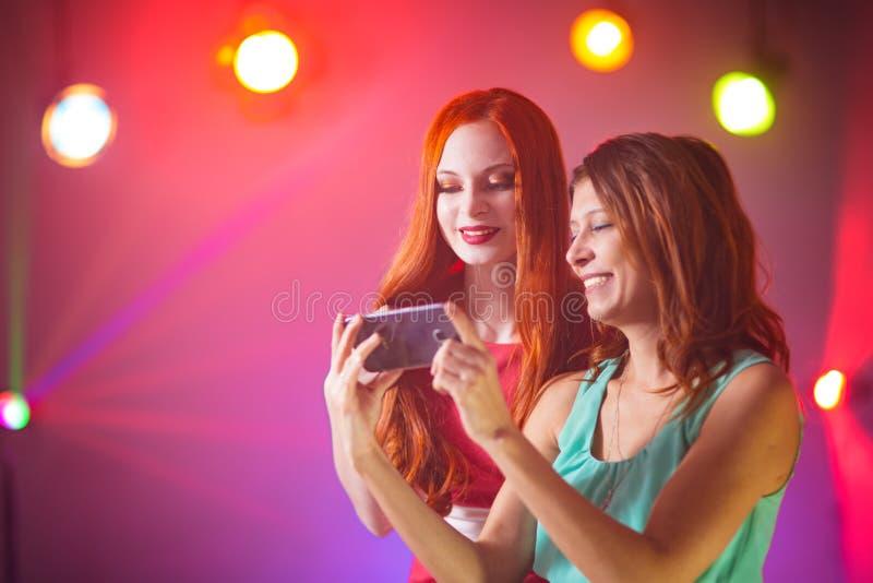 Duas amigas em um clube noturno sob o projetor foto de stock royalty free
