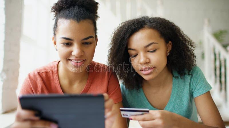 Duas amigas encaracolado alegres da raça misturada que compram em linha com tablet pc e cartão de crédito em casa imagens de stock