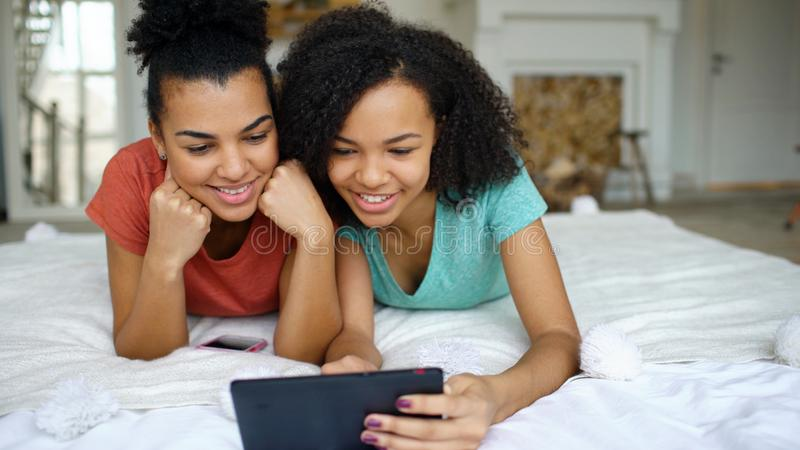 Duas amigas engraçadas alegres da raça misturada que compartilham de meios sociais usando o tablet pc e de negociações que encont fotografia de stock royalty free