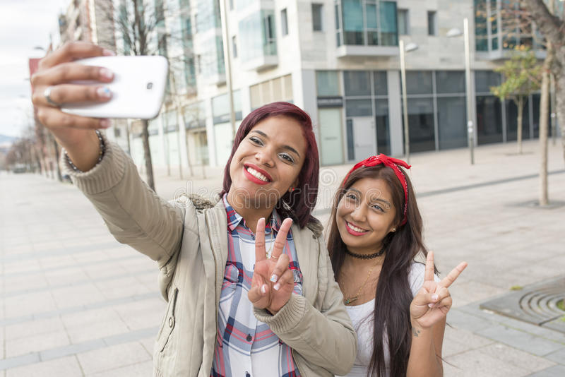 Duas amigas felizes da mulher que tomam um selfie na rua imagens de stock